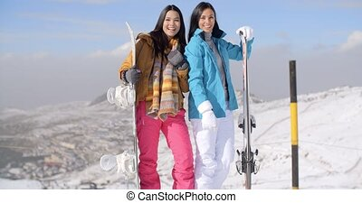 Two young woman with their snowboards