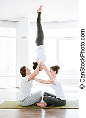 Two young women and man doing acrobatic yoga position
