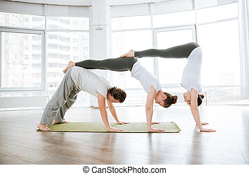 Two young women and man practicing acro yoga