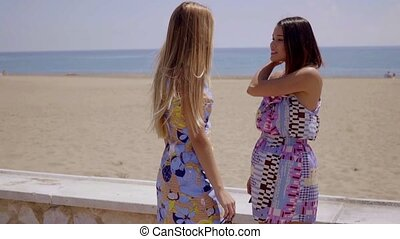 Two young women chatting on a seafront promenade