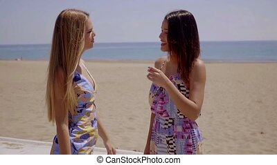 Two young women chatting on a seafront promenade - Two...