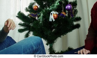Two young women decorating Christmas tree New year preparation having fun