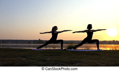 Two Young Women do Warrior 2 Exercises at a Splendid Sunset in Slo-Mo