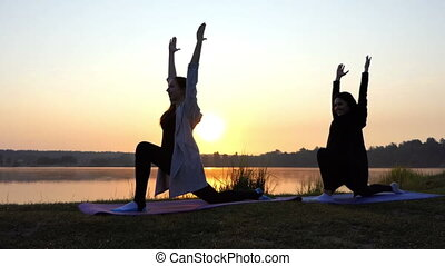Two Young Women do Yoga And Smile on The Splendid Lake Bank at Sunset in Slo-Mo