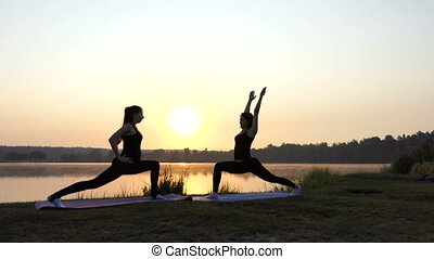 Two Young Women do Yoga Lunge Forward And Warrior Exercises at Sunset