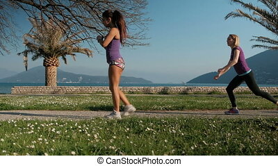 Two young women doing lunges and squats outdoors in summer day.