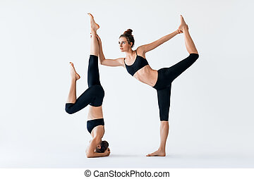 Two young women doing partner yoga asana lord of the dance and Headstand pose