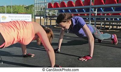 Two young women doing push-ups
