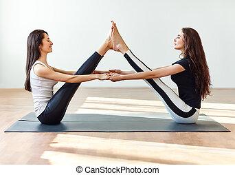 Two young women doing yoga asana buddy boat pose