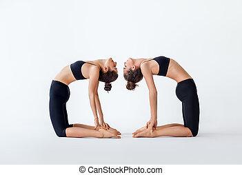 Two young women doing yoga asana camel pose