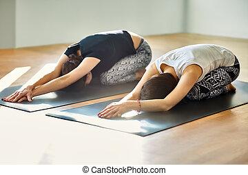Two young women doing yoga asana child's pose. Utthita ...
