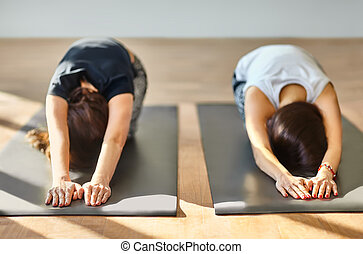 two young women doing yoga asana buddy boat pose