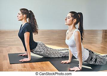 Two young women doing yoga asana cobra pose. Bhujangasana
