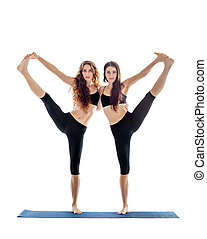 Two young women doing yoga asana extended hand to big toe...