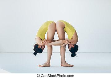 Two young women doing yoga asana standing forward bend pose