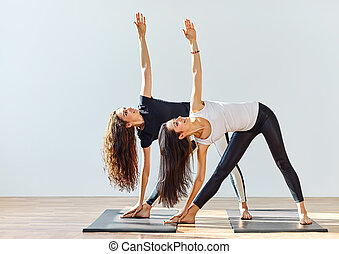 Two young women doing yoga asana extended triangle pose