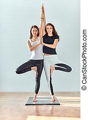 Two young women doing yoga asana tree pose