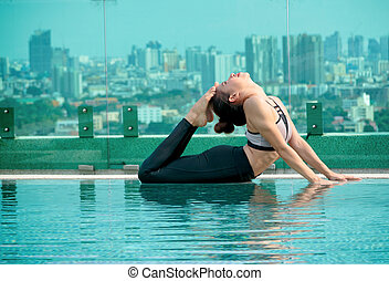 Two young women doing yoga pose at the swimming pool