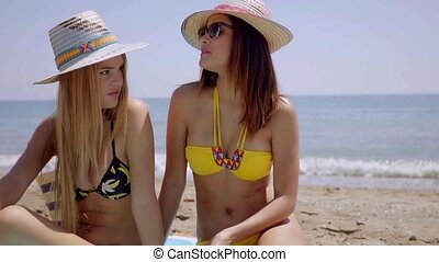Two young women enjoying a day at the beach - Two attractive...