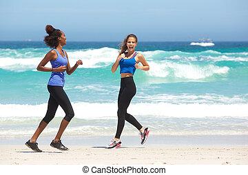 Two young women enjoying a run on the beach