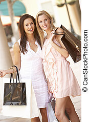 Two Young Women Enjoying Shopping Trip Together