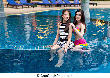 two young women friends enjoy in swimming pool
