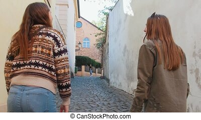 Two young women friends walking on the narrow streets. Mid...