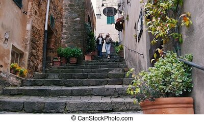 Two young women go up the steps in the alley and drink...