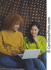 Two young women gossiping and browsing social networks. Multiracial friendship