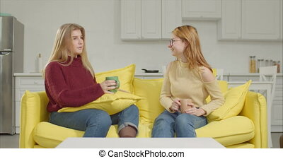Two young women gossipng over coffee on sofa - Positive...