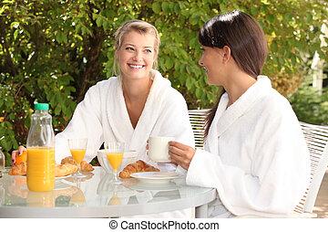 Two young women having breakfast in the garden