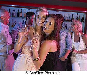 Two Young Women Having Fun In Busy Bar
