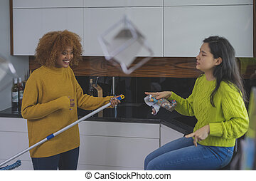 Two young women having fun while doing house cleaning. Multiracial friendship or relationship
