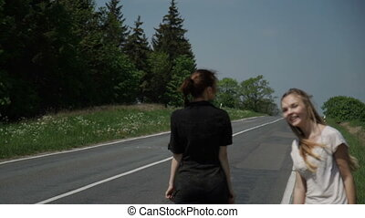 Two young women hitchhikers stand on the sidelines and ask...