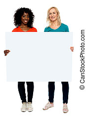 Two young women holding blank billboard