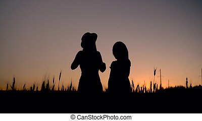Two young women in a dress stand in a wheat field on a sunset background. Black silhouette of girls at sunset