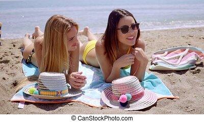 Two young women in bikinis enjoying the beach