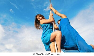 Two young women in blue dresses whirling on the pylon...