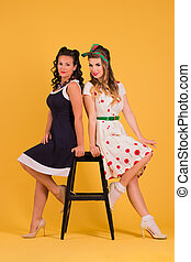 Two young women in dresses pose in yellow studio near stool