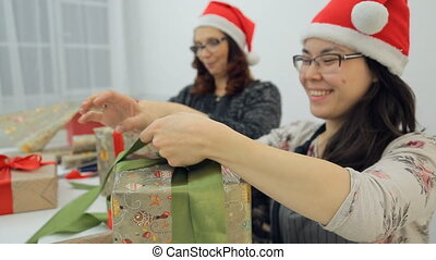 Two young women in glasses and red caps tie bows on gifts and laugh.