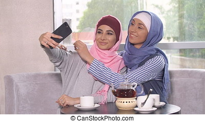 Two young women in hijabs do selfie on a smartphone. Muslim women in a cafe
