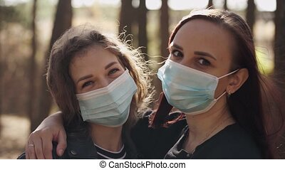 Two young women in medical masks look at camera in wood. Close up of females protecting yourself from diseases on walk. Concept of threat of coronavirus epidemic infection