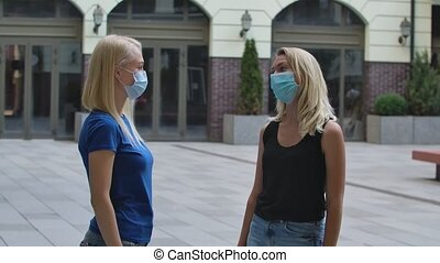 Two young women in protective medical masks greet each other...