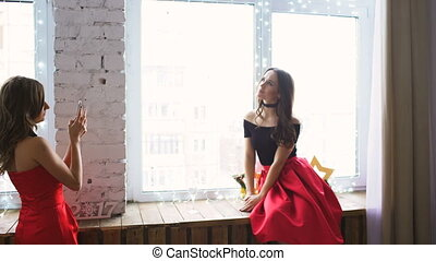 Two young women in red cocktail dress posing and photograps at smartphone on window