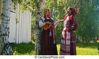 Two young women in russian dresses standing on the meadow -...
