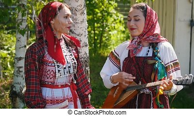 Two young women in Russian traditional dress stand under a...
