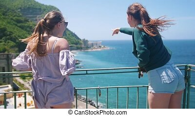 Two young women in small shorts standing on an observation...