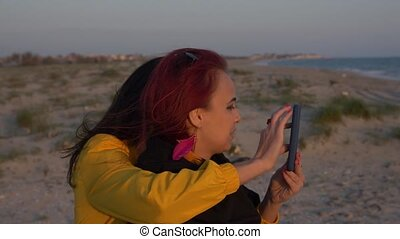 two young women in the gentle rays of the sunset on the background of the sea surf embraced and look at the phone