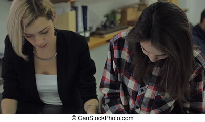 Two young women in the office look at some documents and talking, a man sitting behind them