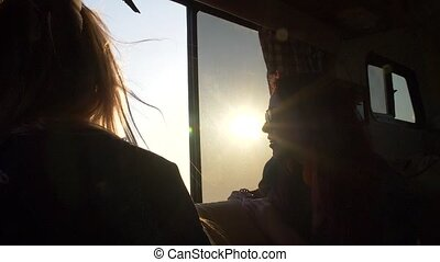 two young women in the sun and glare look through the window of the trailer on a deserted beach